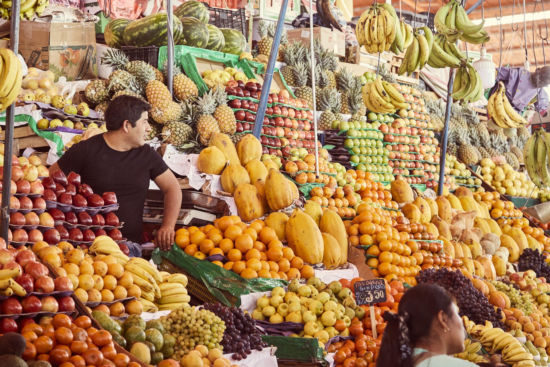 San Camilo Market in Peru, Arequipa, Obstverkäufer umgeben von Bergen aus Früchten
