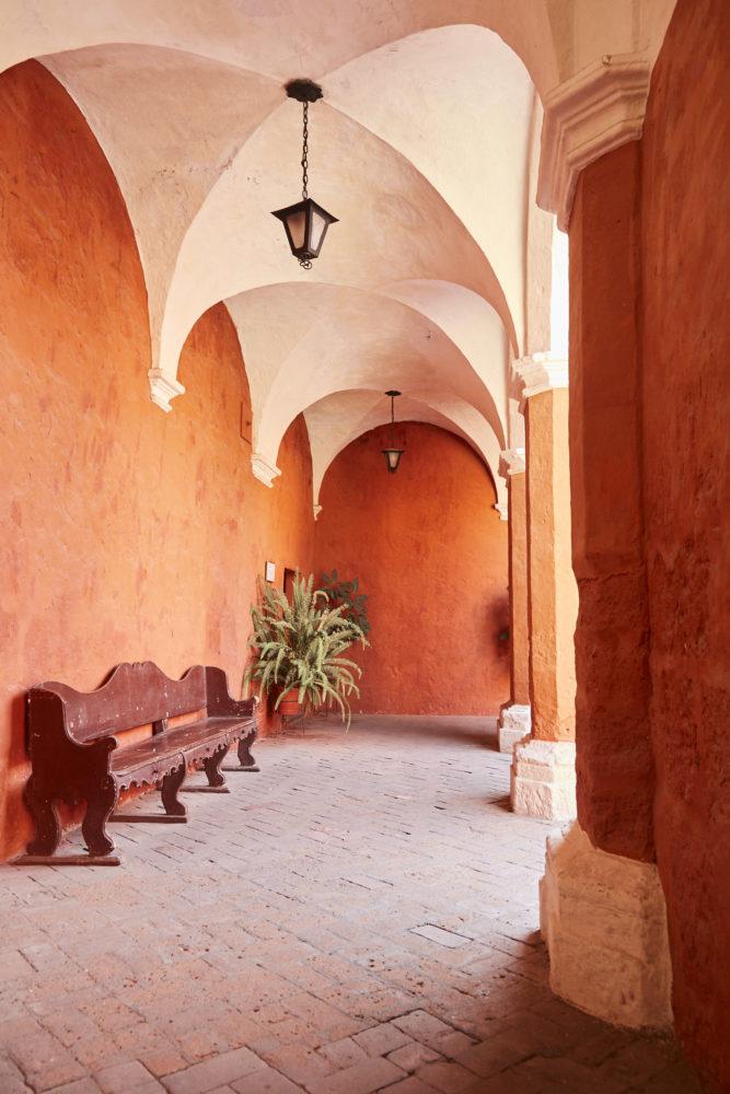 Rotes Gewölbe mit weißer decke und roter Parkbank im Kloster Santa Catalina in Peru