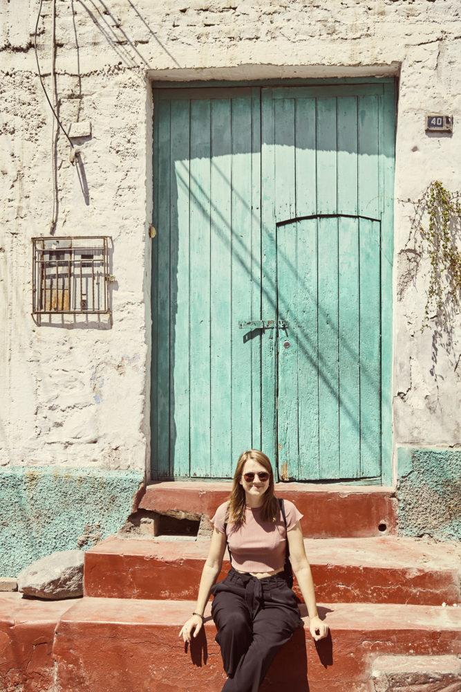 Reiseblogger Christina von Miles and Shores sitzt vor türkiser Eingangstür in Arequipa im Stadtteil Yanahuara