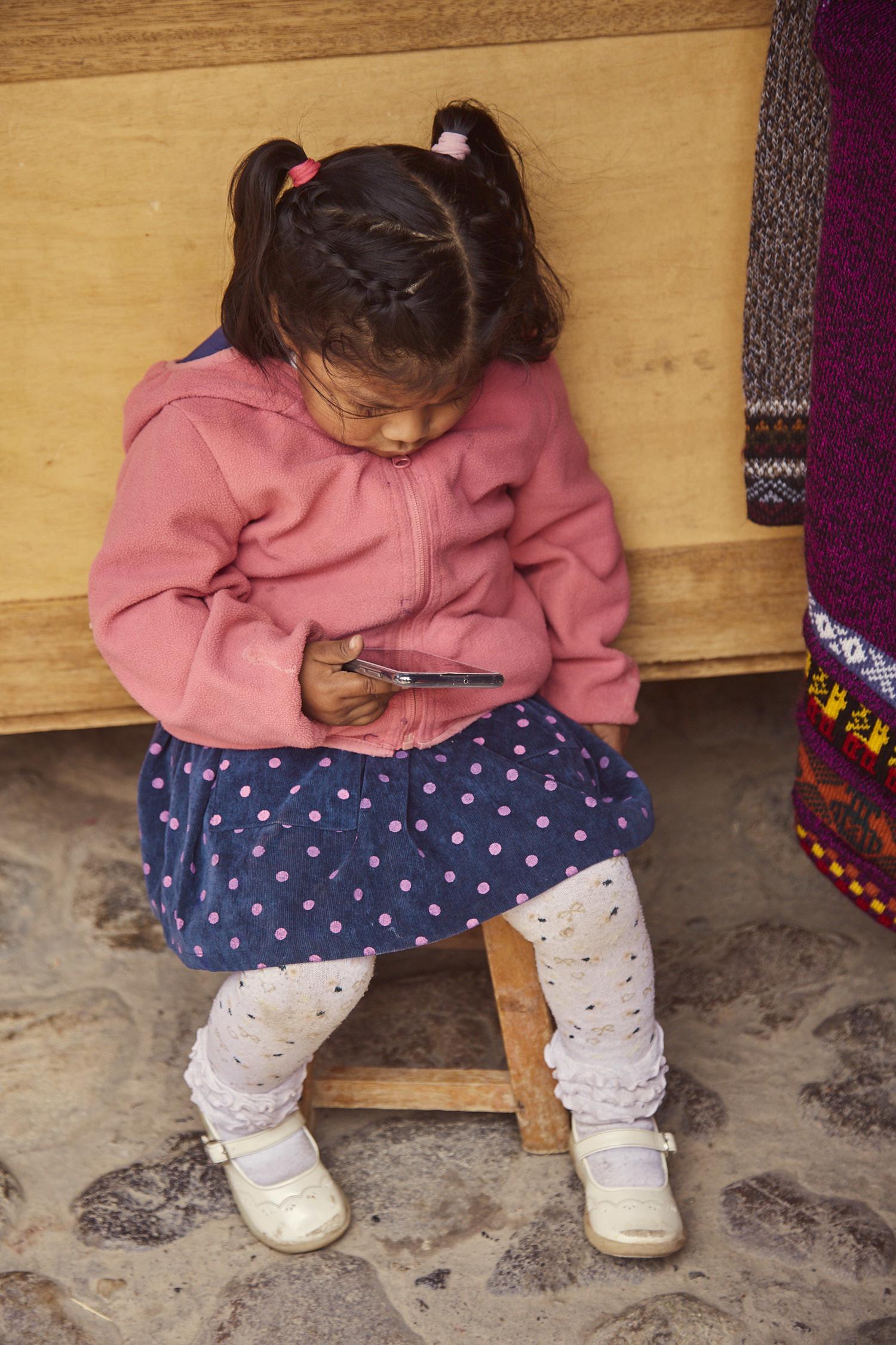 Kleines Kind in Peru mit Handy in der Hand. Internet in Peru macht absolut Sinn! Das Handynetz ist sehr gut ausgebaut!