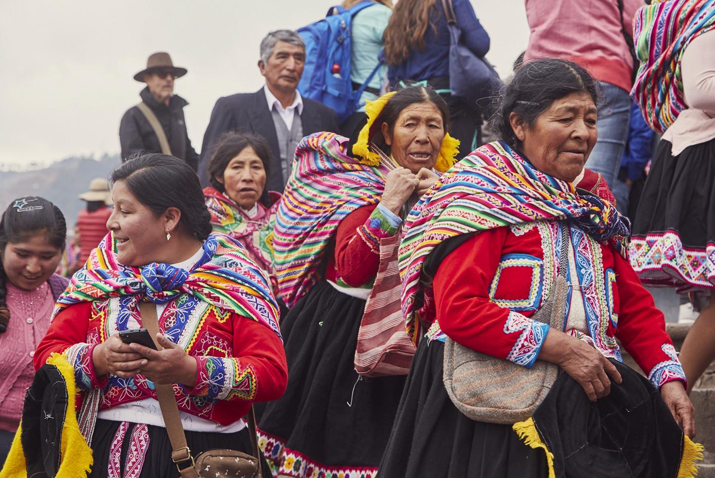 Peruanerinnen in traditioneller Kleidung in Cusco. Eine der Damen hält ein Telefon in der Hand