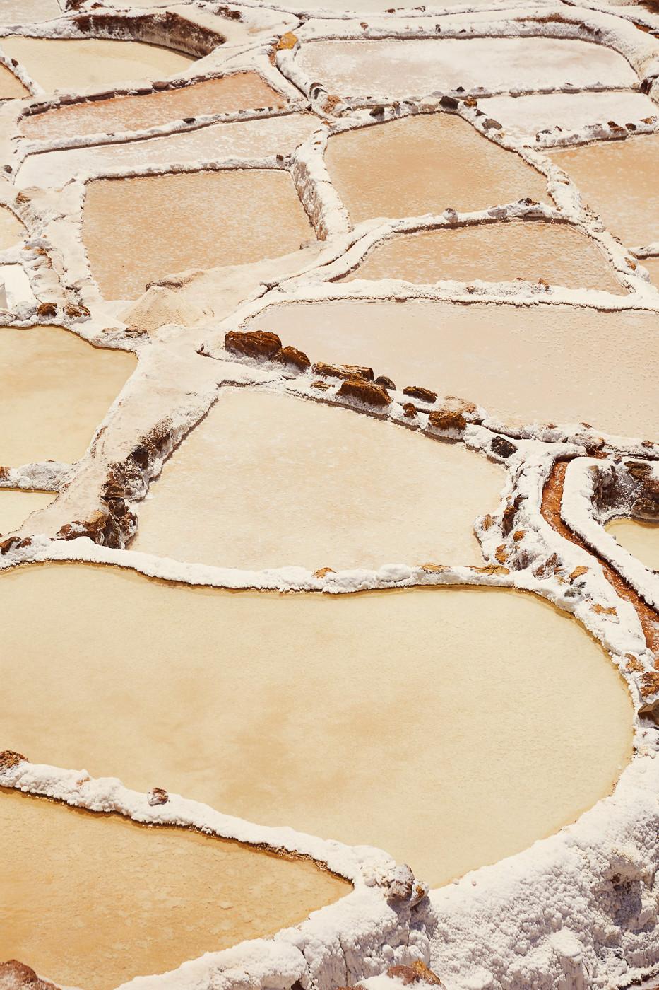 Die Salzminen Salineras de Maras in Peru, farbige Salzfelder in warmen Farben
