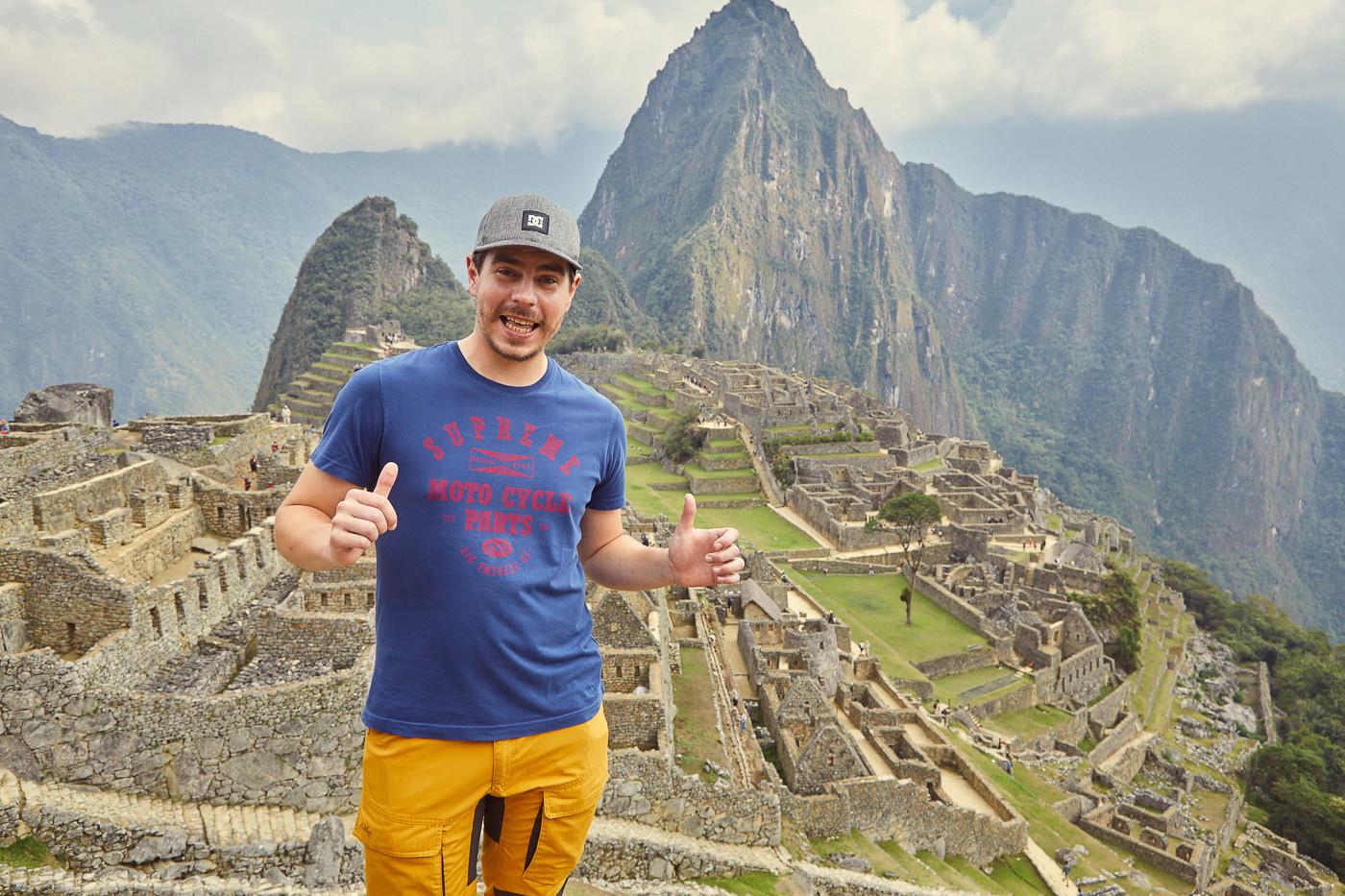 Ronnie vor Machu Picchu, Peru. In unserem Guide erzählen wir, welche Möglichkeiten es gibt, nach Machu Picchu zu kommen, von der neuen Zugstation in Cusco, und was du alles NICHT dabei haben solltest, wenn du nach Machu Picchu reist.
