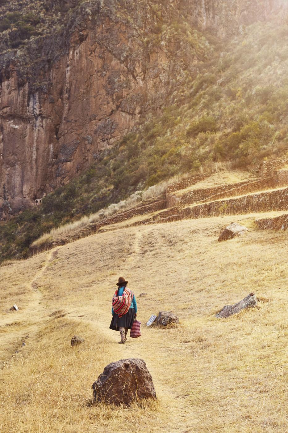 Die Peruanerin läuft entlang der Terrassen der Pisac Ruinen. Sie ist auf dem Weg nach Hause in den Ort Pisac unterhalb der peruanischen Ruinen