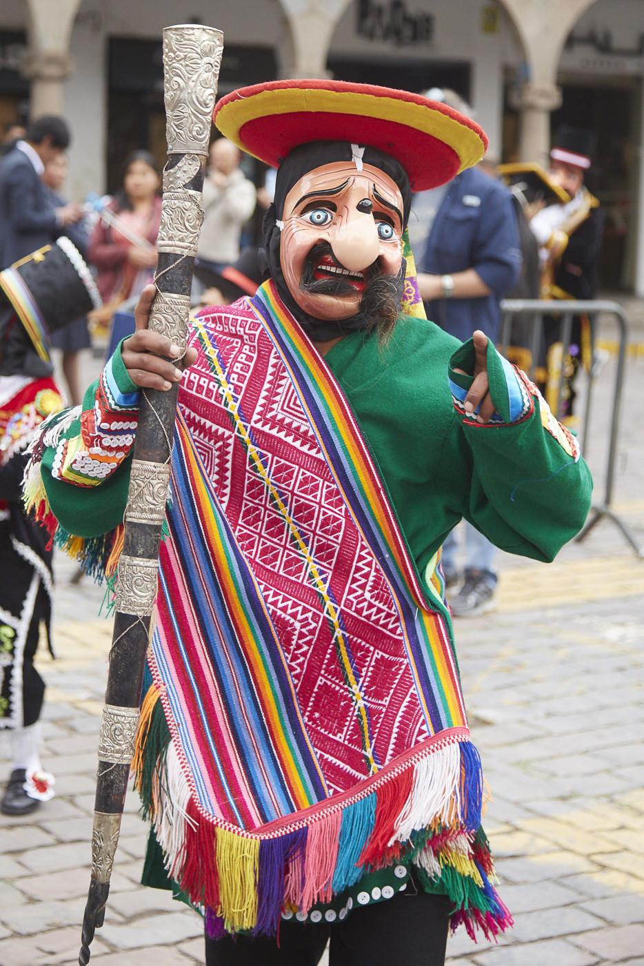 Maske mit Knollnase, Sombrero und Schnauzbart, ein grüner Pulli und eine mit buntem Muster bestickte Scherpe trug dieser Teilnehmer der Parade in Cusco