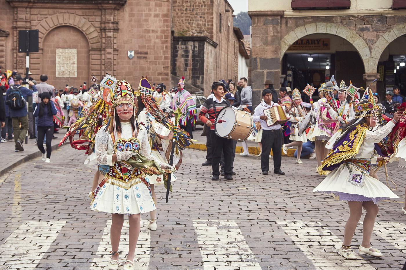 Frauen mit bemalten Holzmasken, kurzen Röcken und Federschmuck, dahinter die Straßenmusikanten in den Straßen von Cusco