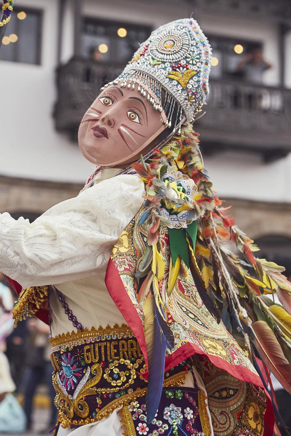Frau mit bemalter Holzmaske, Federschmuck und einer Art Krone beim Umzug zur Fiesta del Señor de Huanca in Cusco, Peru