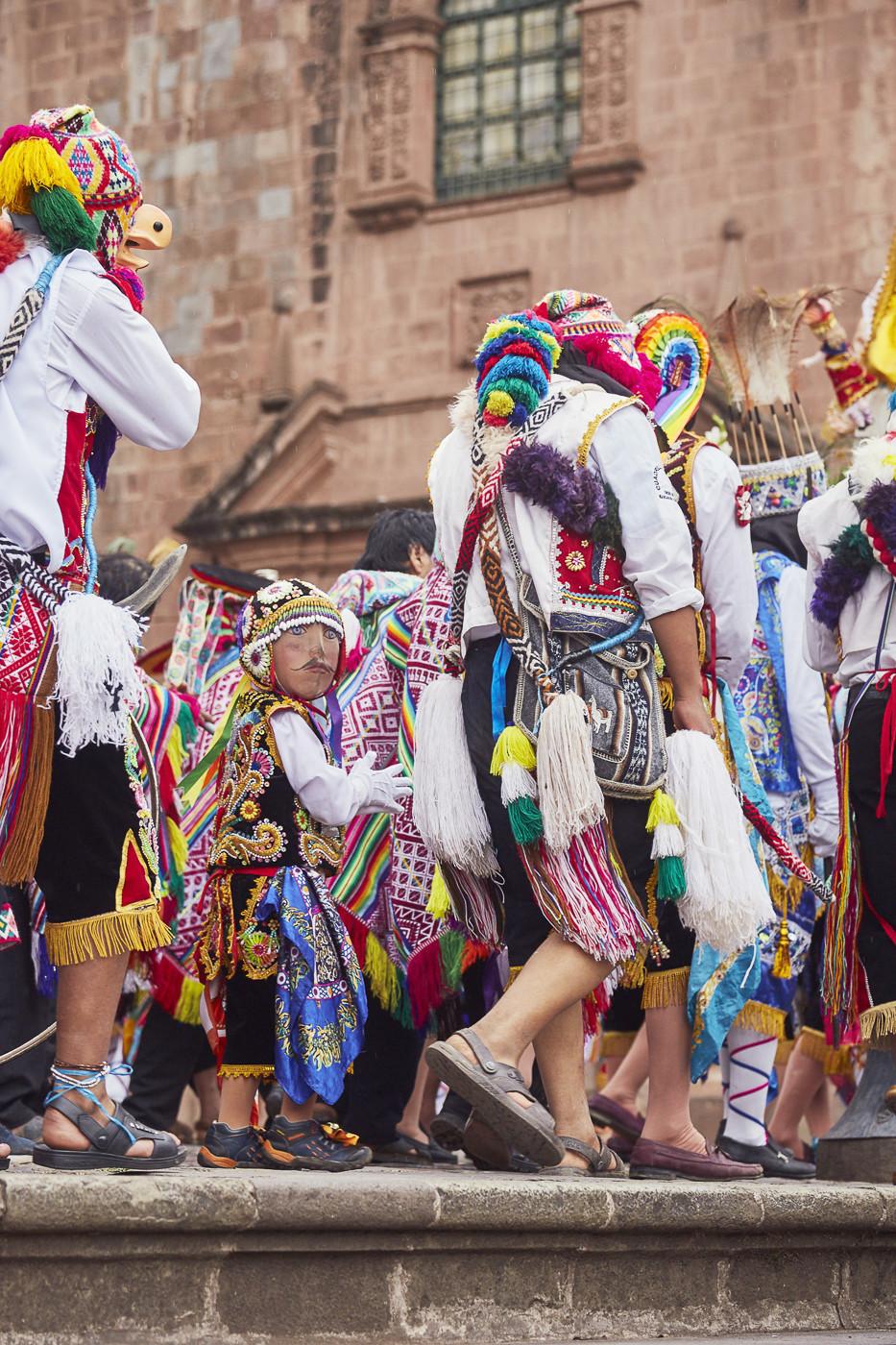 Kinder mit Masken halten die Hände ihrer Eltern in der Parade