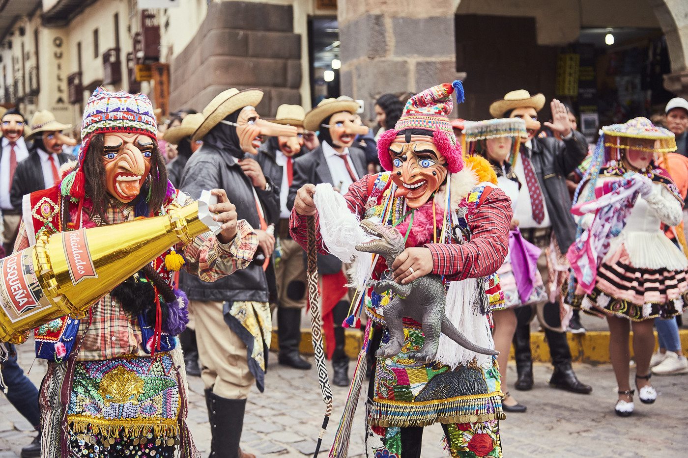 Auch lustige, moderne Gestalten sieht man auf der Parade: zwei Gestalten mit Masken, die die Zunge zeigen, Mützen, einer großen Flasche Champagner und einem T-Rex in der Hand