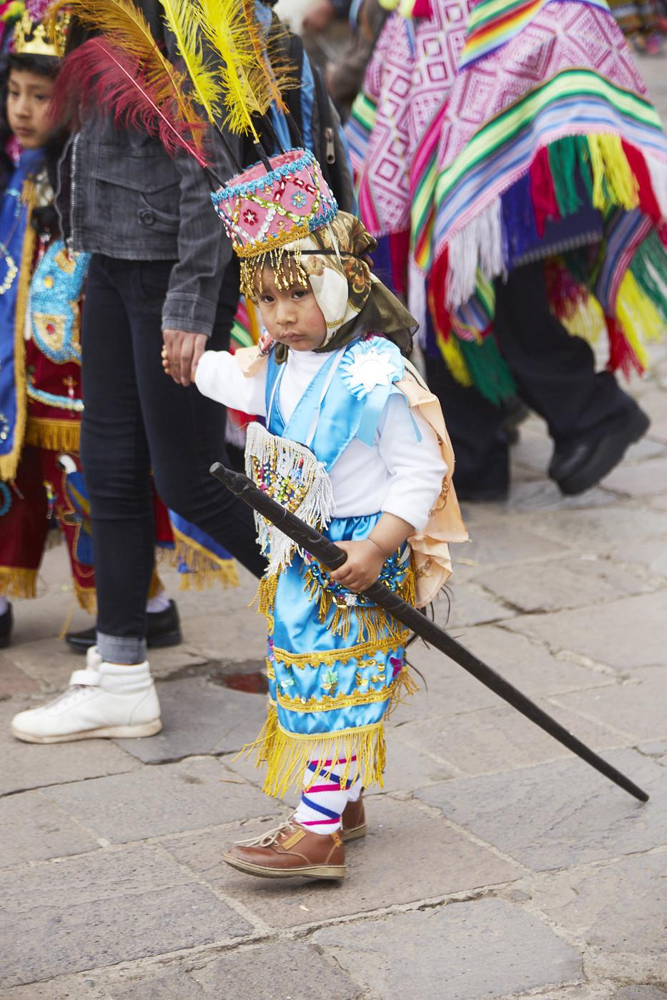 Kind verkleidet, vermutlich als Inka König, in blauem Gewand, Kopfschmuck mit Federn und einem Gehstock