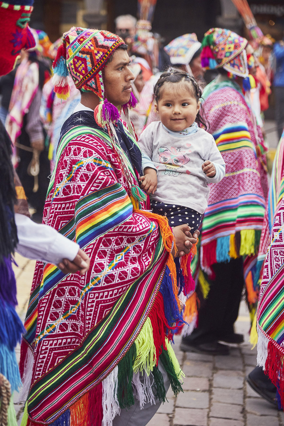 Mann in peruanischer Tracht mit kleinem lachenden Kind auf dem Arm - Kultur in Peru