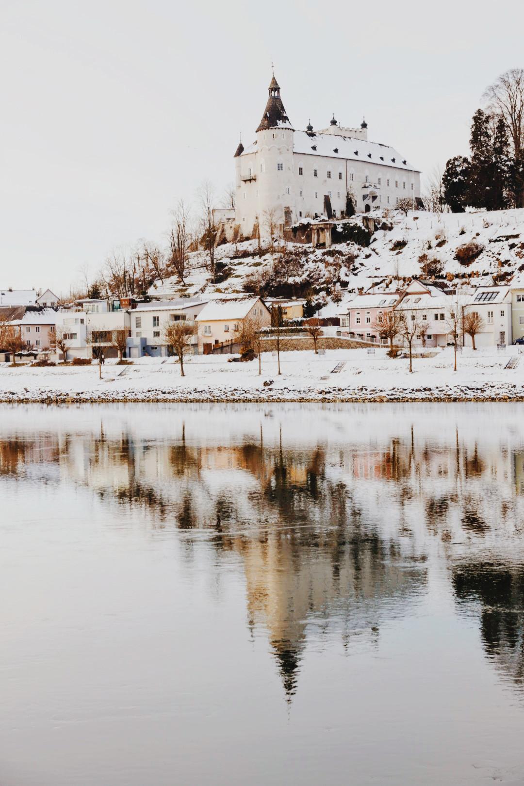 Auch Urlaub zu Hause kann schön sein: Das Schloss Ottensheim in Oberösterreich in Schneelandschaft